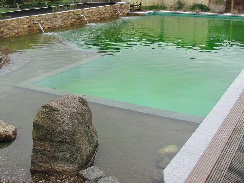 Schwimmteich mit Wasserschwall